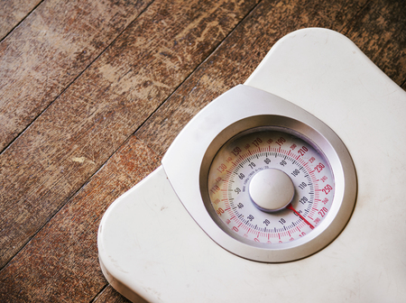 Old analog weight scale on wood floor