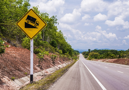 downgrade: steep downgrade warning signs and truck on hill  Stock Photo