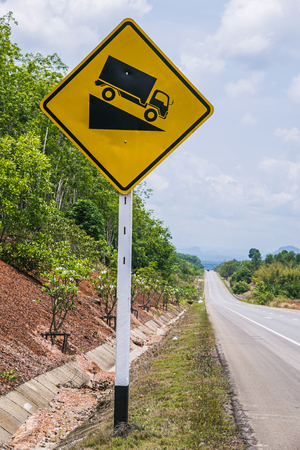 downgrade: steep road sign with a truck driving down a steep downgrade on blue sky background  Stock Photo