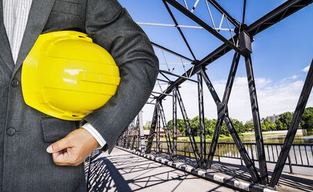 Engineer hand holding yellow helmet for workers security against historical railway bridge over the ping river ,Chiang Mai- Thailand   Stock Photo