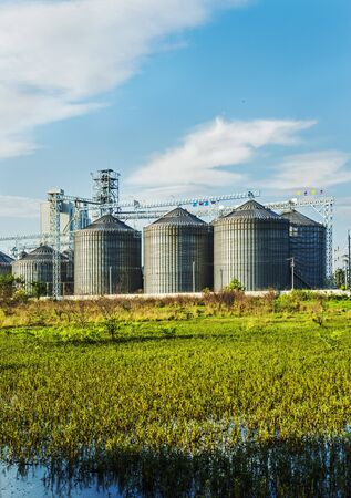 rice mill: Cereal silos under the blue sky. Editorial