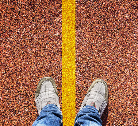 A pair of feet standing on a running track rubber with a yellow stripe. photo