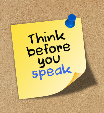 Think before you speak written on yellow note pinned on cork board.  Stock Photo