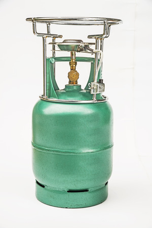 Portable stove on gas cylinder isolated on white  photo
