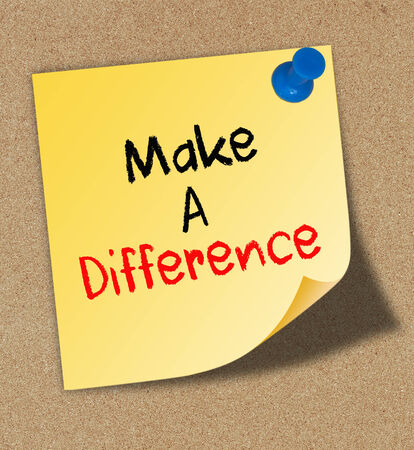 Make A Difference written on an yellow sticky note pinned on a cork bulletin board.  photo