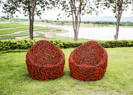 Round modern furniture plastic wicker chairs on grass in relax garden