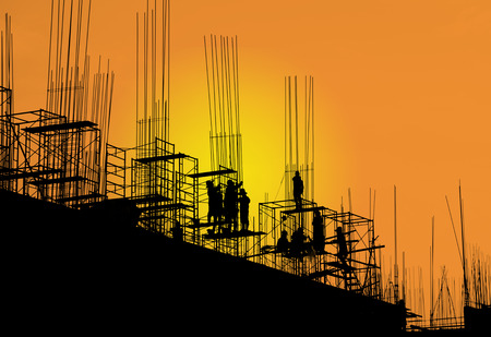 Silhouette workers on scaffolding steel in sunset background Foto de archivo
