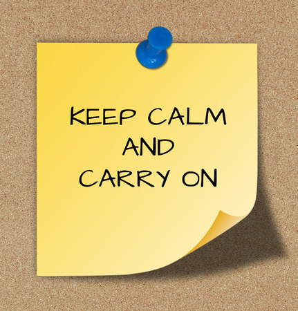 The words keep calm and carry on, slogan on yellow paper.  photo