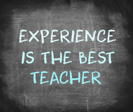 Experience is the best teacher saying written on blackboard .