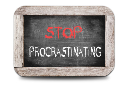 Stop Procrastinating handwritten on chalkboard