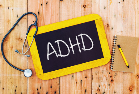 ADHD handwritten on blackboard , medecine concept.