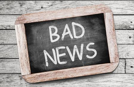Bad news written on chalkboard