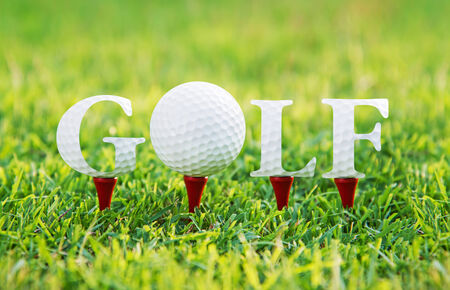GOLF word on red tee and green grass background photo