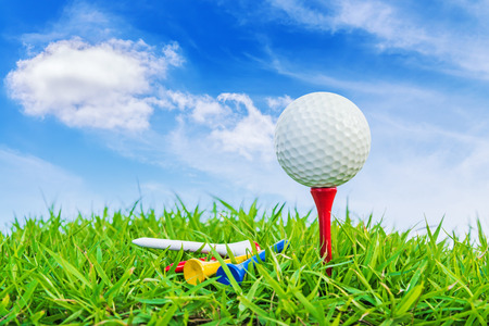 Golf ball on a tee against a blue sky and white clouds.