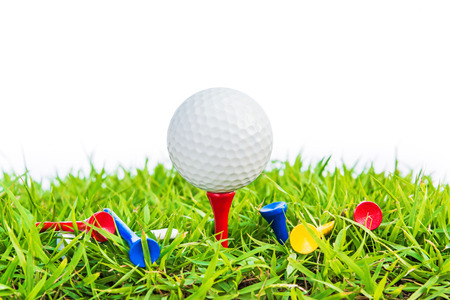 Golf ball on green grass against white background, selective focus. photo