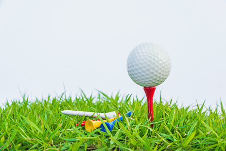 Golf ball on green grass against white background. photo