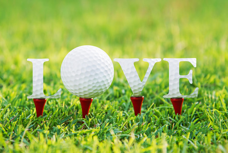 Golf letters word LOVE on green grass.