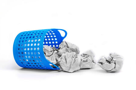 meaningless: Trash basket filled with crumbled paper canted on a side isolated on white background