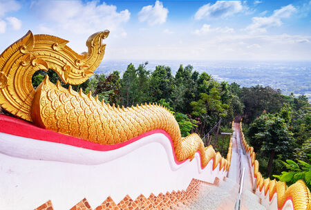 stair well: Golden Naka statue on staircase balustrade at Thai Buddhist pagoda, Wat Phra That Doi Kham, Temple in Chiang Mai, Thailand Stock Photo