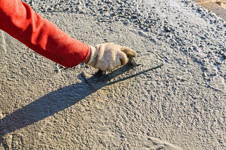 concrete: Construction worker spreading wet poured concrete