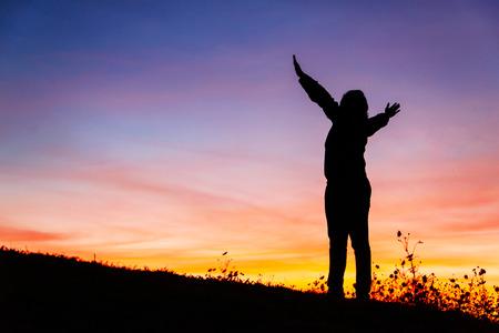 Silhouet van een christelijke vrouw is bidden tegen zonsondergang