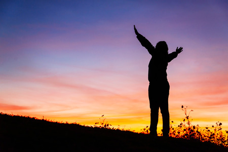 Silhouette of a Christian woman is praying against sunset Stock Photo - 34813723