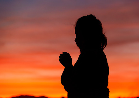 in need of space: Silhouette of a Christian woman is praying against sunset Stock Photo