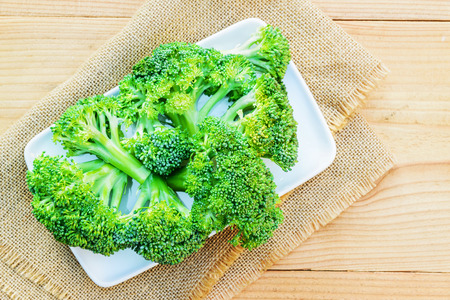 Broccoli vegetable in white plate on wood background Stock fotó
