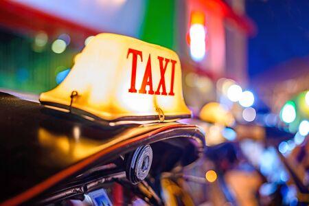 tuk: Thai Taxi (Tuk Tuk) sign with defocused lights blur , Chiang Mai, Thailand.