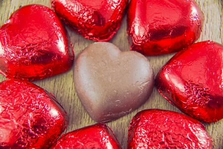 fancy sweet box: Heart shaped chocolates on a wood background.