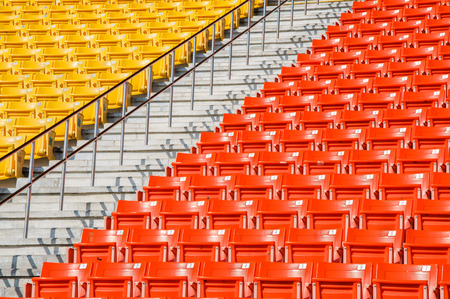 Empty orange and yellow seats at stadium.