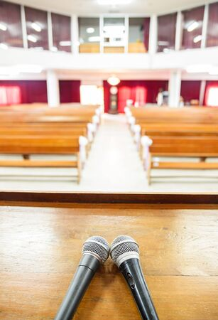 pews: Closeup microphone in empty church with empty pews