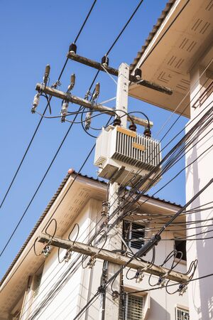 isolator insulator: Transformers of an electrical post with powerlines against bright blue sky. Stock Photo