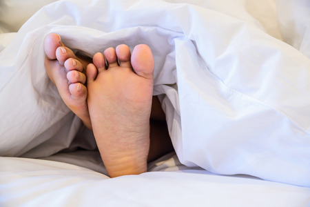 sleep well: Close up of two feet in a bed against  white background.
