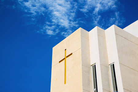 Cross on church over blue sky and clouds