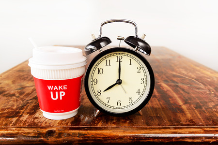 seven o'clock: Alarm clock and coffee cup, eight oclock in the morning Stock Photo