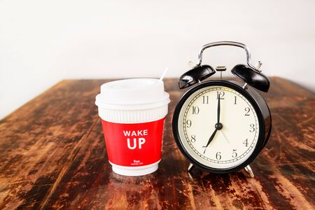 seven o'clock: Alarm clock and coffee cup, seven oclock in the morning.