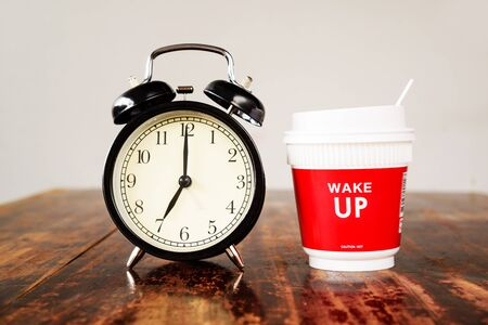 o'clock: Alarm clock and coffee cup, seven oclock in the morning.