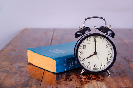 Holy bible and alarm clock on wood table.