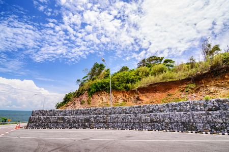 Gabion wall made of stones in the steel mesh, used as a fence on a slope.