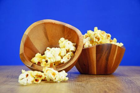 bowls of popcorn: Popcorn in a wooden bowl on wood floor Stock Photo