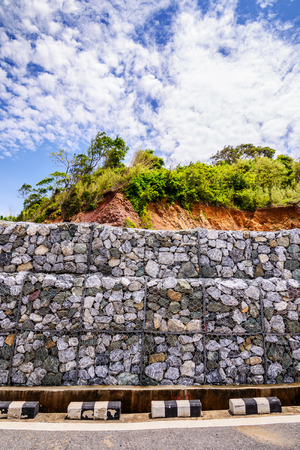 gabion mesh: Gabion wall made of stones in the steel mesh, used as a fence on a slope.