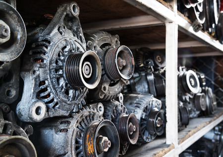 pulleys: Old car alternators on shelf.