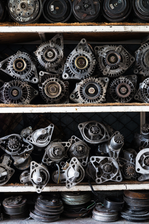 aluminum wheels: Old car alternators and starter motor car on shelf.