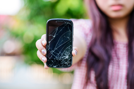 Girl hand holding cracked mobile smartphone Stock Photo