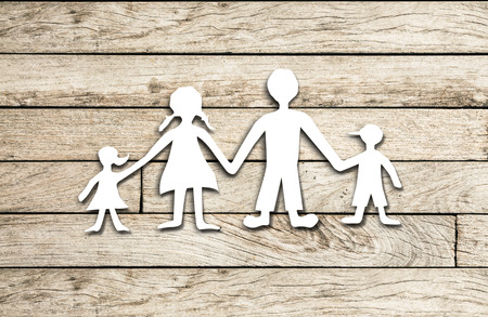 adopting: Happy family paper cut on wood background Stock Photo