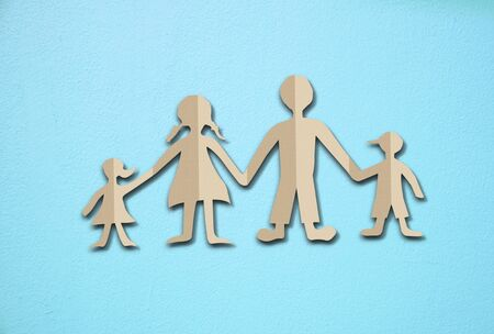 adopting: Happy family paper cut on cement wall background