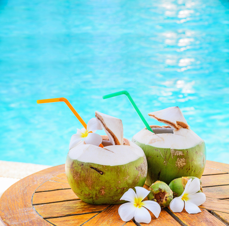 Green coconuts and flower on wood table at swimming pool in summer.