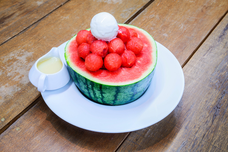sweetened: Watermelon granita and icecream in watermelon with sweetened Condensed Milk on wooden table. Stock Photo