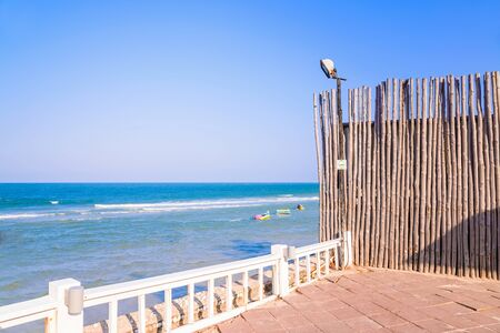 beach front: Wooden fence on a beach , front of a blue sea Stock Photo